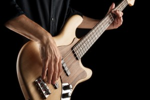bassist hands playing a jazz bass guitar on black background